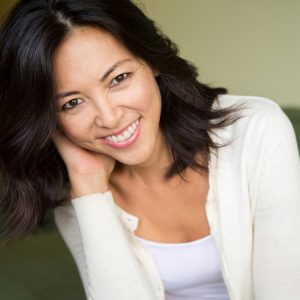Image of a happy lady who learned that in addition to tooth extractions, we also offer gentle family dentistry.